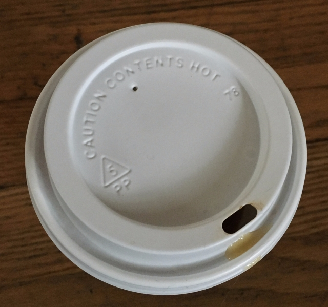 Adult sippy cup lid, with boiling tea seeping over the edge