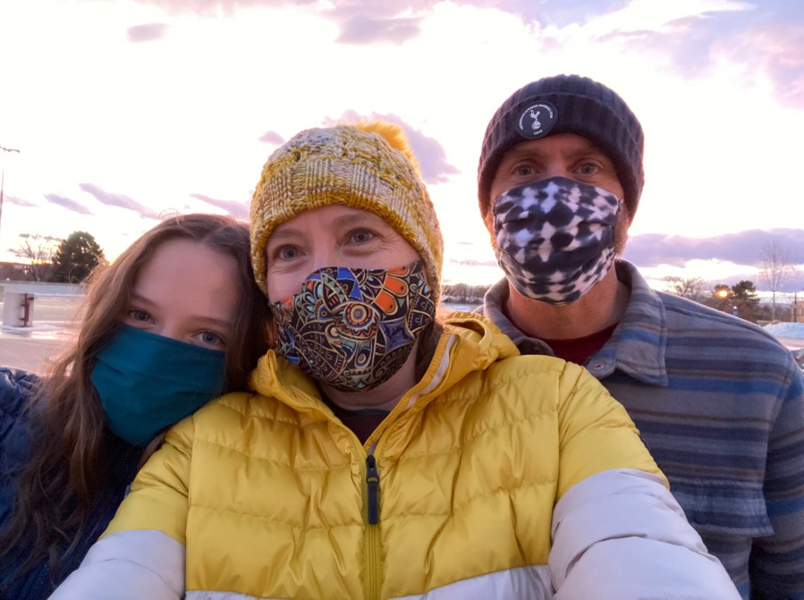 A family with masks on and a sunset behind them.